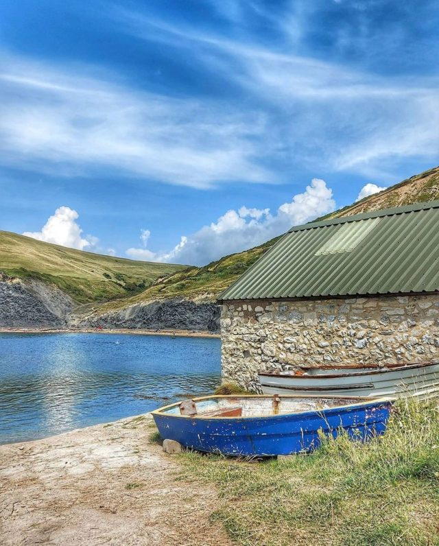 """My Jurassic Coast by @lotten.in.dorset.  """"Picture perfect little boats and their boathouses at Chapman's Pool 🛶  The cove really is as calm and beautiful as it looks. The descent (or rather eventual ascent) is all worth it and this little hidden paradise couldn't be any more soothing for the soul 🌿  As a Scandinavian living in England the bay feels like home away from home as it is reminiscent of the 'badplatser' from my childhood. Badplatser is the plural of badplats which just means a 'bathing place' so whilst a beach could technically be a badplats it is more common that it is these rocky type terrains that you can find across Sweden whether in the archipelagos or around the lakes.  A huge part of Swedish summer culture! Sweden is magical and Dorset is bringing that magic closer to home"""".  #myjurassiccoast #chapmanspool"""