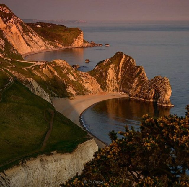 """My Jurassic Coast by @jo_bugler70.  """"My favourite place on the Jurassic Coast has to be Durdle Door, which I try to visit, out of season, as much as I can.  The ancient geology of the door stands proudly & majestically along the East Dorset coastline.  Over the years I have enjoyed swimming & kayaking, early morning fishing, photography adventures and many picnics with my family on the beach.  All truly memorable  experiences in a place of such natural beauty.   I feel very lucky to live so close to the Jurassic Coast as a whole, with the many beautiful bays & diverse landscapes to explore.  A feast for the vision & soul.   #myjurassiccoast #durdledoor #jurassiccoast #worldheritagesite"""