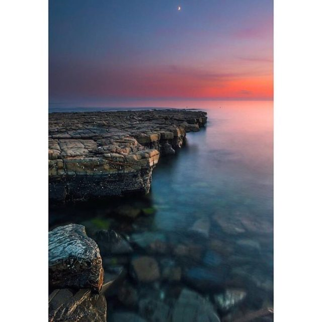 "This beautiful photograph of Broadbench was chosen by our 1,200th follower @georgebaylis as his favourite recent moment on the Jurassic Coast. ""Gin clear water, pink skies and the light of the silvery moon"". George is a photographer, artist and works for an organisation providing advocacy work for vulnerable adults. If you have a chance, enjoy a look through his feed which is full of inspirational images. Thank you George. . . #jurassiccoast #kimmeridge"